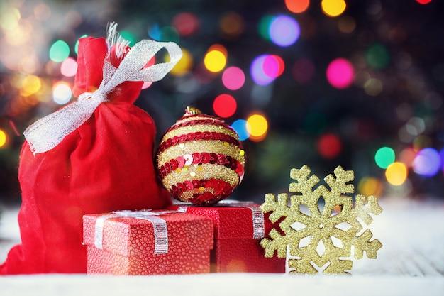 Cadeaux de noël décorés et sac de père noël sur fond festif coloré
