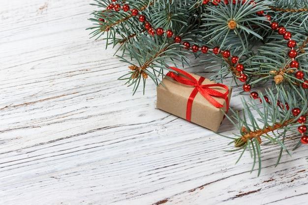 Cadeaux de noël ou du nouvel an enveloppés dans du papier de couleur naturelle et décorés avec de la ficelle de noël traditionnelle et des brindilles de sapin sur fond blanc