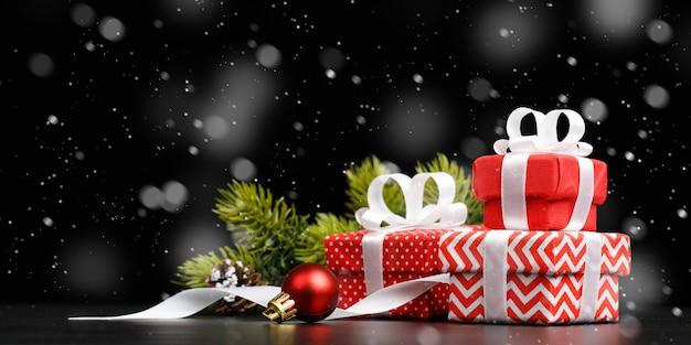 Cadeaux de noël et du nouvel an. pile de coffret rouge avec des décorations sur fond noir.