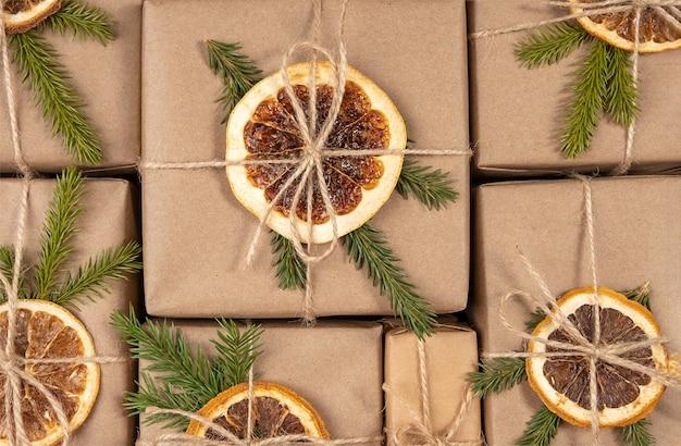 Les cadeaux de noël et du nouvel an se bouchent. boîtes en papier artisanal décorées d'oranges séchées, de branches d'épinette et de ficelle. concept zéro déchet, écologique joyeux noël.