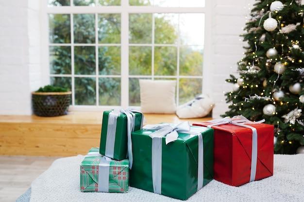 Cadeaux de noël élégants sur le lit près de l'arbre de noël et de la fenêtre.