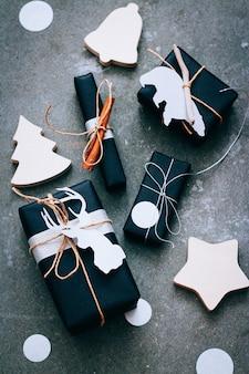 Cadeaux de noël en emballage noir avec étiquettes, confettis et décor en bois sur fond gris
