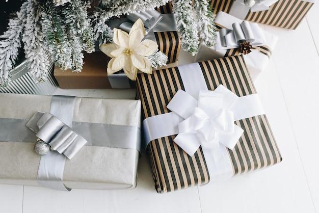 Cadeaux de noël emballés à côté de l'arbre de noël