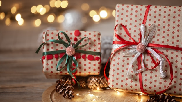 Cadeaux de noël emballés dans du papier kraft avec des rubans, des guirlandes et des cônes décoratifs sur fond flou.