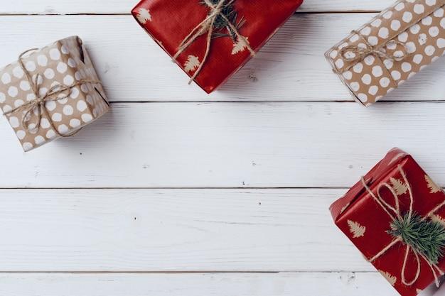 Cadeaux de noël emballés sur planche de bois blanc, vue du dessus, espace copie