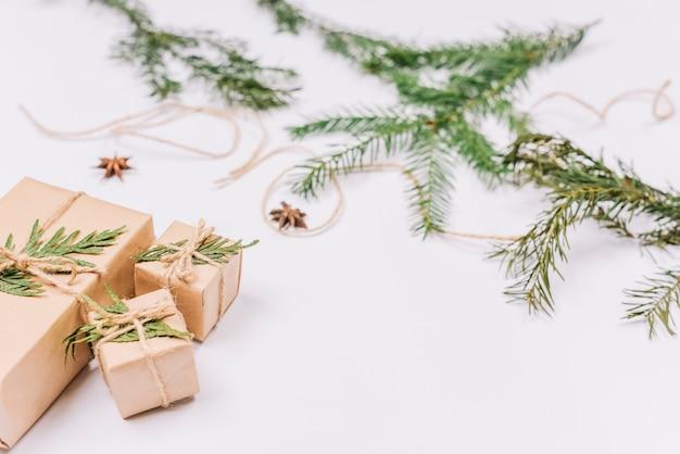 Cadeaux de noël emballés près de branches de conifères