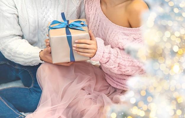 Cadeaux de noël entre les mains d'un homme et d'une femme, mise au point sélective.