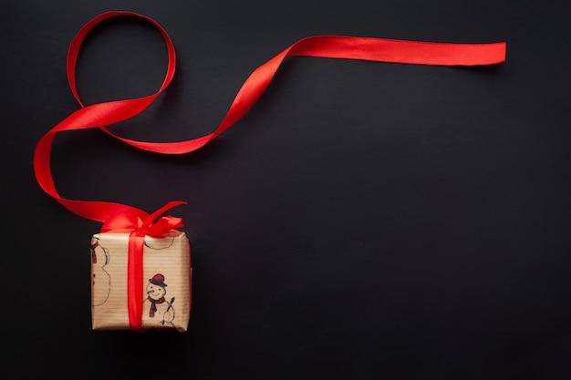 Cadeaux de noël enveloppés dans un ruban rouge sur fond noir