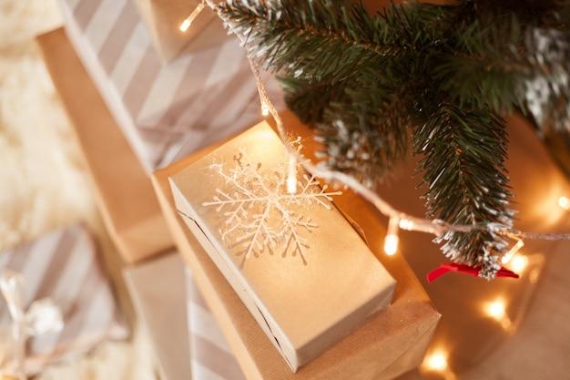Cadeaux de noël enveloppés avec guirlande sous l'arbre de noël, célébrations du nouvel an, cadeaux de noël en gros plan.