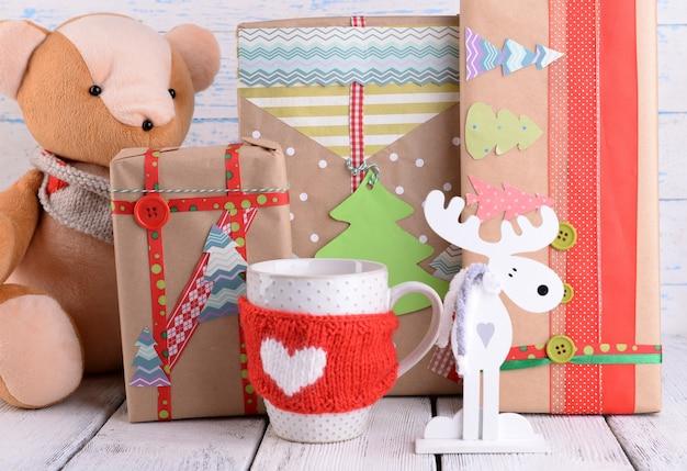 Cadeaux de noël faits à la main avec des décorations sur une surface en bois