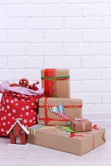 Cadeaux de noël faits à la main et sac de noël avec des boules sur le sol dans la chambre