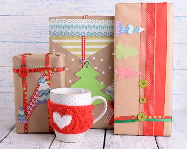 Cadeaux de noël faits à la main avec une tasse de café sur une surface en bois