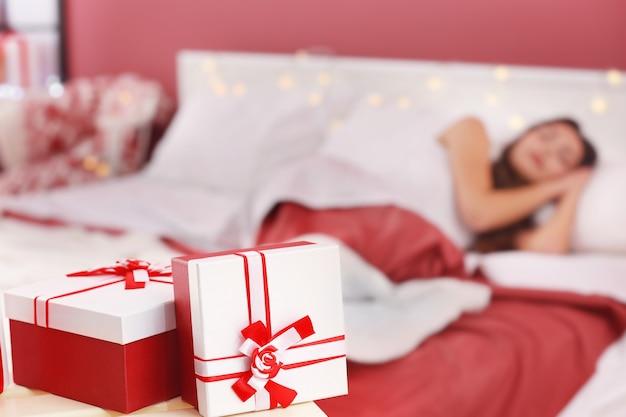 Cadeaux de noël et femme endormie floue