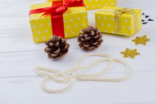 Cadeaux de noël fond collier de perles pommes de pin et coffrets cadeaux humeur vacances d'hiver