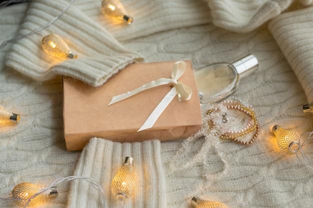 Cadeaux de noël et guirlandes lumineuses sur un pull chaud et confortable, vue de dessus.