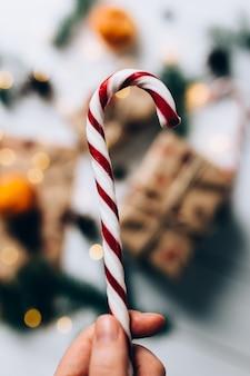 Cadeaux de noël, main tient la sucette, mandarine sur fond de bois blanc. photo de haute qualité