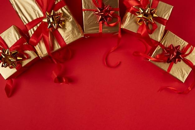 Cadeaux de noël en papier doré avec un ruban rouge