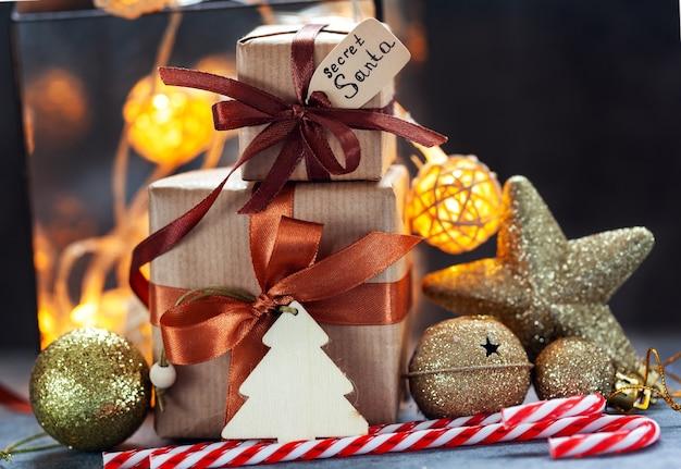 Cadeaux de noël papier kraft emballé avec décoration de vacances et lumières sur fond sombre
