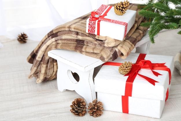 Cadeaux de noël près de l'arbre de noël sur une surface en bois