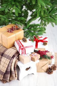Cadeaux de noël près de l'arbre de noël sur une surface claire