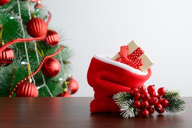Cadeaux de noël en sac sur table sur fond de sapin.