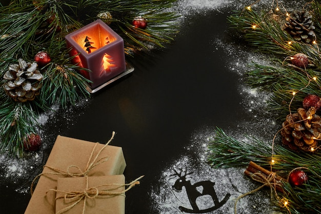 Cadeaux de noël, sapin de noël, bougies, décor coloré, étoiles, boules sur fond noir. vue de dessus. espace de copie. nature morte à plat lay nouvel an