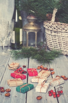 Cadeaux de noël, sorbier des oiseleurs, noix, étalés sur des tableaux blancs peints rugueux. au fond, panier, lampe ancienne et bouteille de vin