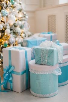 Cadeaux de noël sous l'arbre décoré en bleu