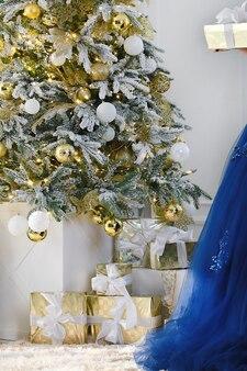 Cadeaux de noël sous un fond d'arbre de noël décoré partie d'une élégante robe bleue