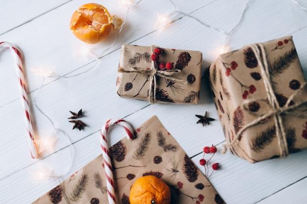 Cadeaux de noël, sucette, mandarine sur fond de bois blanc. photo de haute qualité