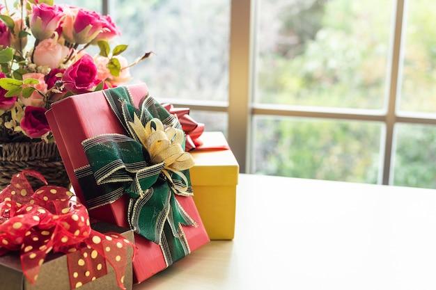 Cadeaux de noël avec vase rose et bonnet de noel sur la table en bois intérieur de la salle vue par la fenêtre avec arbre
