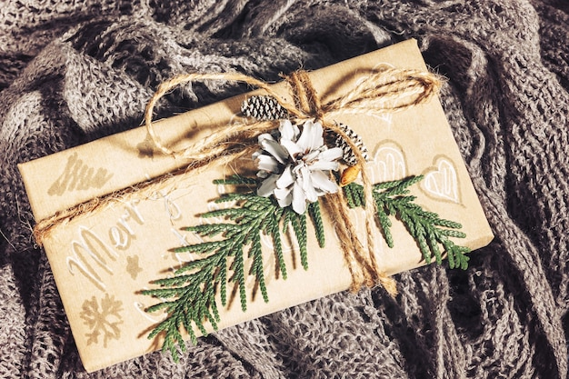 Cadeaux de noël vintage avec coffret décoré de pommes de pin et de brindilles sur un tissu en coton