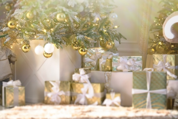 Cadeaux de nouvel an de luxe différentes boîtes présentes sous l'arbre de noël fond de vacances defocus