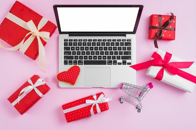 Cadeaux et panier d'achat autour d'un ordinateur portable et d'un coeur