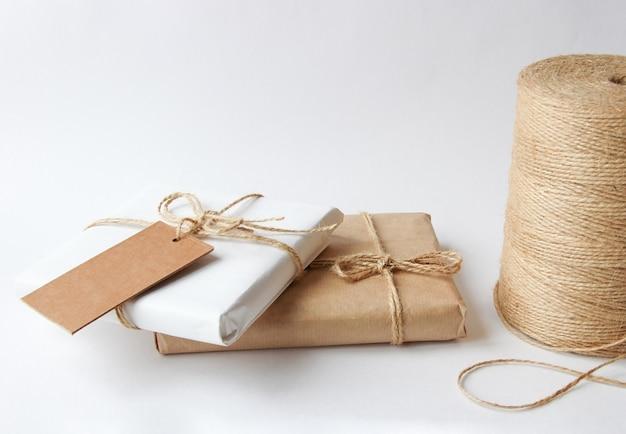 Cadeaux en papier kraft attachés avec une corde sur fond clair