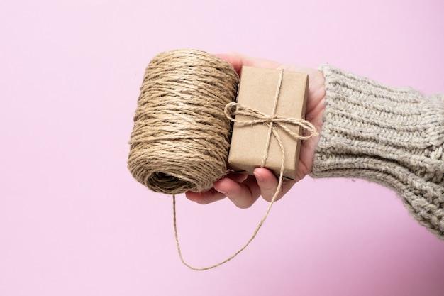 Cadeaux en papier kraft, une bobine de corde dans les mains des femmes sur fond rose, gros plan. concept de cadeaux faits à la main. tendance moderne, emballage cadeau naturel de vos propres mains. fond de vacances.