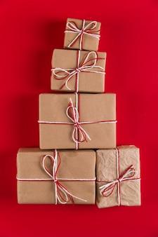 Cadeaux de papier kraft et de cordes en forme de sapin de noël sur une surface rouge, noël, de cartes de voeux.