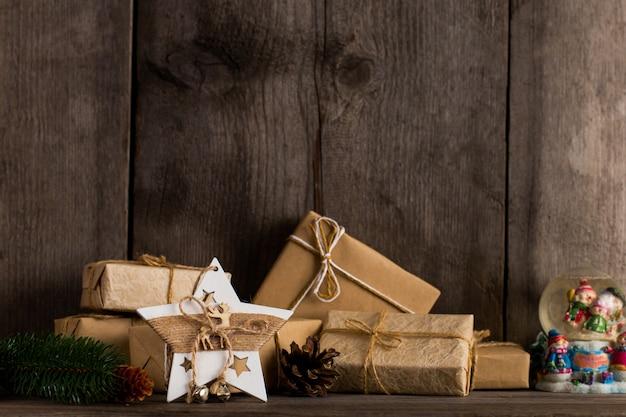 Des cadeaux en papier kraft et une décoration d'étoile de noël sur une ancienne étagère en bois.