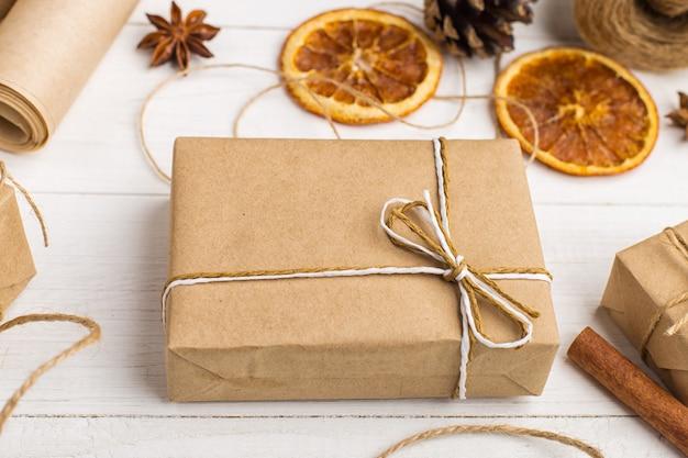 Cadeaux en papier kraft, orange séchée, cannelle, pommes de pin, anis sur une table blanche