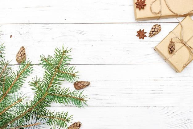 Cadeaux pour le nouvel an enveloppés dans du papier kraft près de branches d'épinette et de cônes sur la vue de dessus de fond en bois blanc