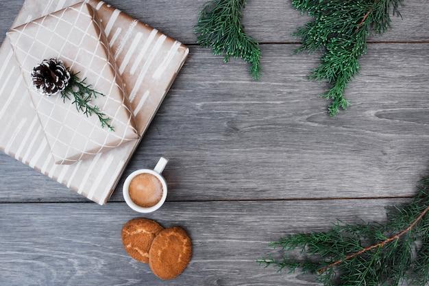 Cadeaux près de brindilles, tasse de boisson et biscuits