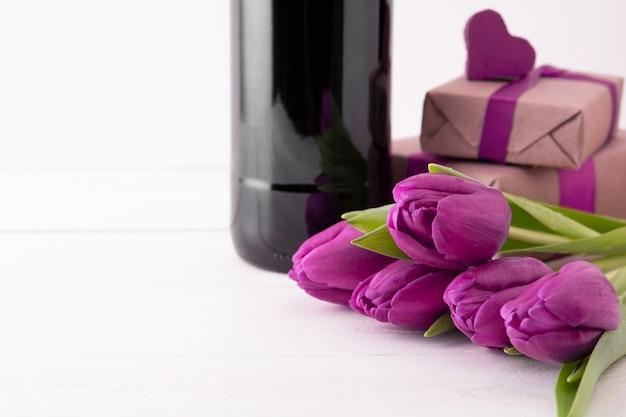 Cadeaux romantiques avec fleurs et vin sur mur blanc