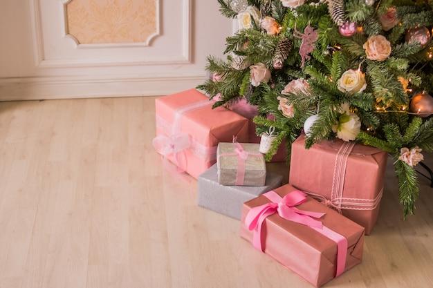 Cadeaux roses pour noël sous un arbre de noël décoré