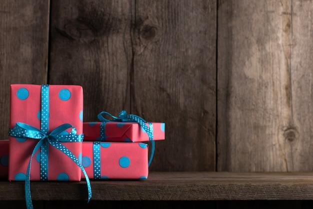 Cadeaux roses avec ruban bleu sur une ancienne étagère en bois.