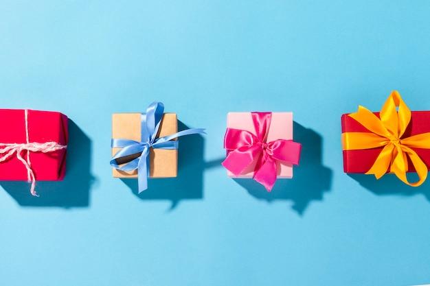 Cadeaux avec un ruban sur fond bleu sous la lumière naturelle. moderne. vacances, famille, bien-aimés, pour lui. mise à plat, vue de dessus