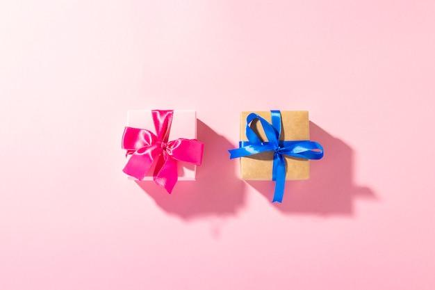 Cadeaux avec un ruban sur fond rose sous lumière naturelle. moderne. vacances, famille, bien-aimés, pour lui. bannière. mise à plat, vue de dessus