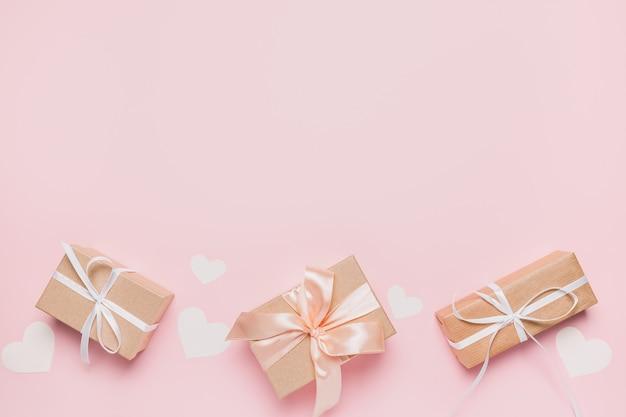 Cadeaux avec ruban wihte sur fond rose isolé, concept d'amour et de valentine