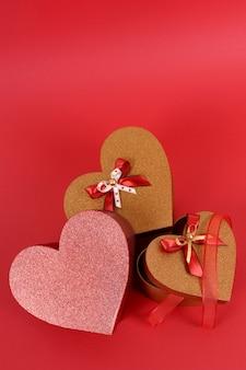 Cadeaux saint valentin scintillant rouge et or sur fond de papier rouge.