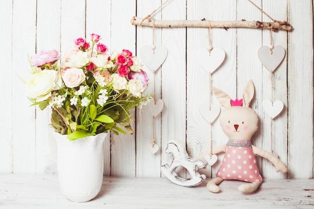 Cadeaux de la saint-valentin tels que rose dans un vase blanc, tasse blanche, bougies parfumées, cadres vides et lapin jouet