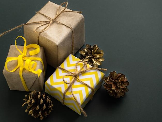 Les cadeaux sont emballés dans du papier kraft et décorés dans un style jaune.